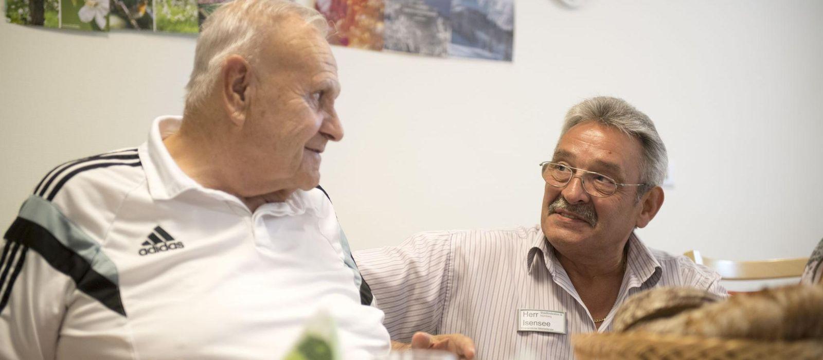 Ein Bewohner eines Seniorenheimes und ein ehrenamtlicher Mitarbeitender sitzen gemeinsam am Tisch.