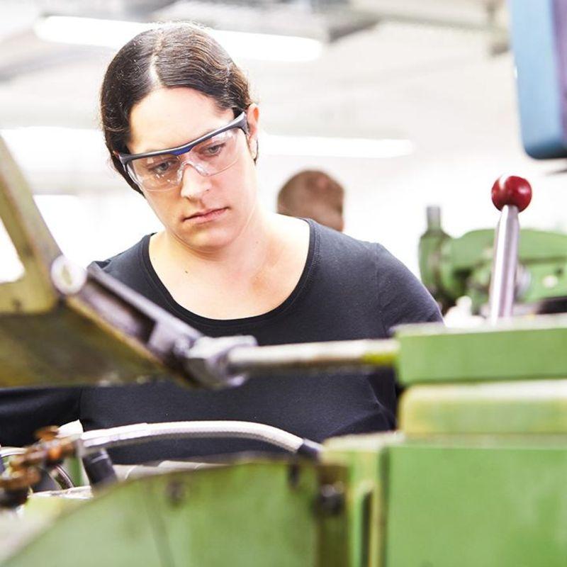 Eine junge Frau steht mit Schutzbrille an einer Maschine.