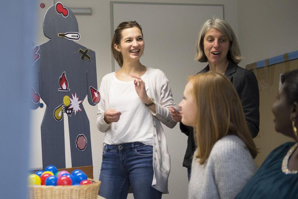 Zwei Frauen stehen vor einer Pappfigur und erklären Dinge.