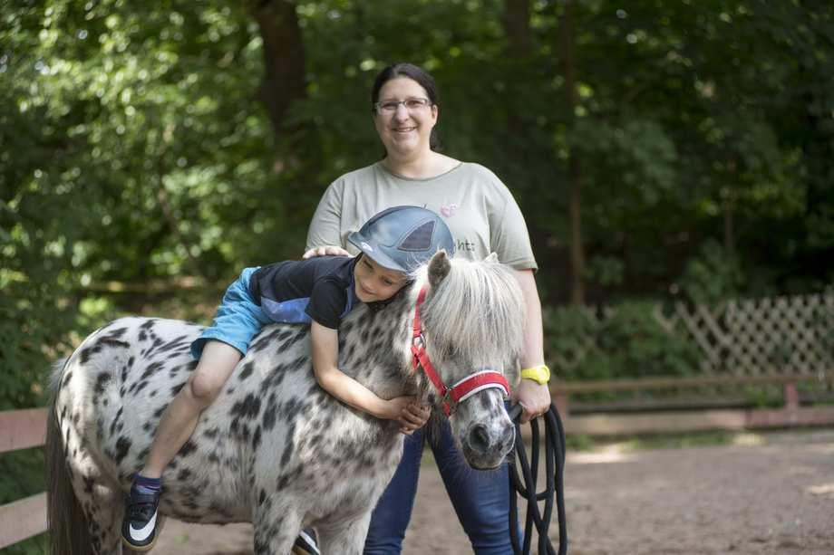 Ein Junge liegt auf einem Pony. Er hat die Arme um den Hals des Tieres geschlungen. Neben dem Pferd steht eine Frau, hält die Longe und lächelt.