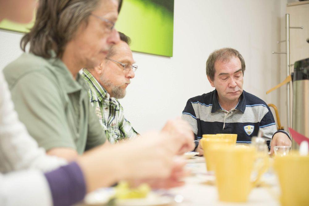 Drei Männer sitzen an einem Frühstückstisch mit gelben Tassen.