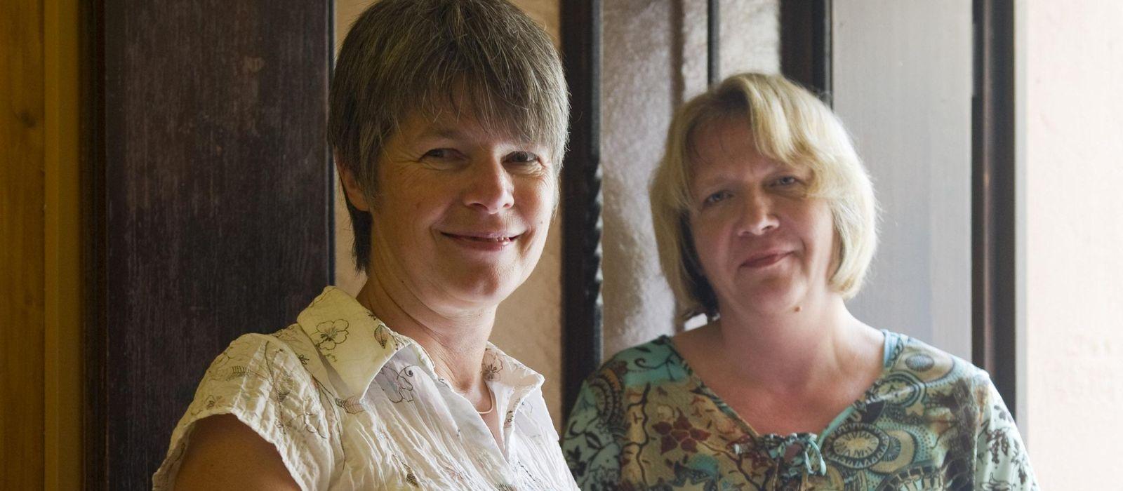 Zwei Frauen stehen in einer Tür und lächeln.