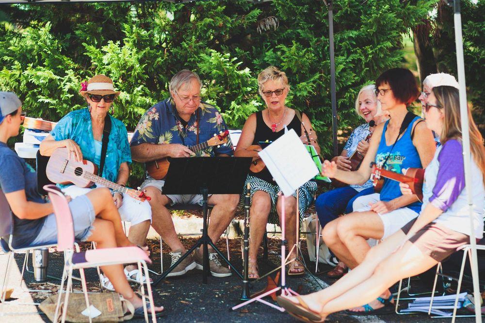 Acht Personen sitzen in einem Stuhlkreis im Freien und musizieren gemeinsam.
