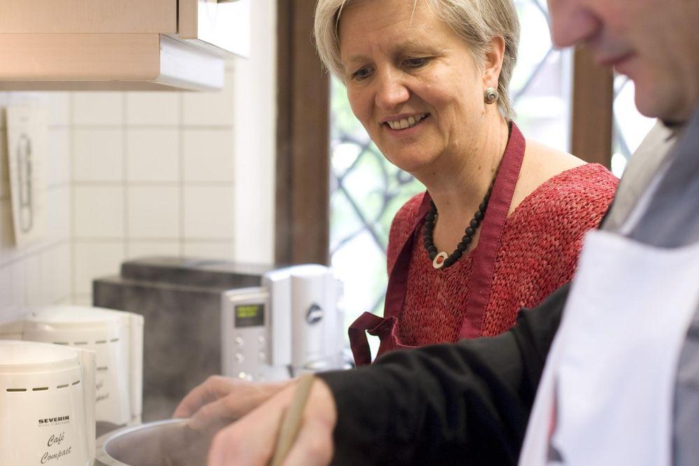 Eine Frau und ein Mann, die in der Küche stehen. Der Mann hat einen Kochlöffel in der Hand und rührt etwas im Topf um. Die Frau schaut ihm dabei zu und lächelt.