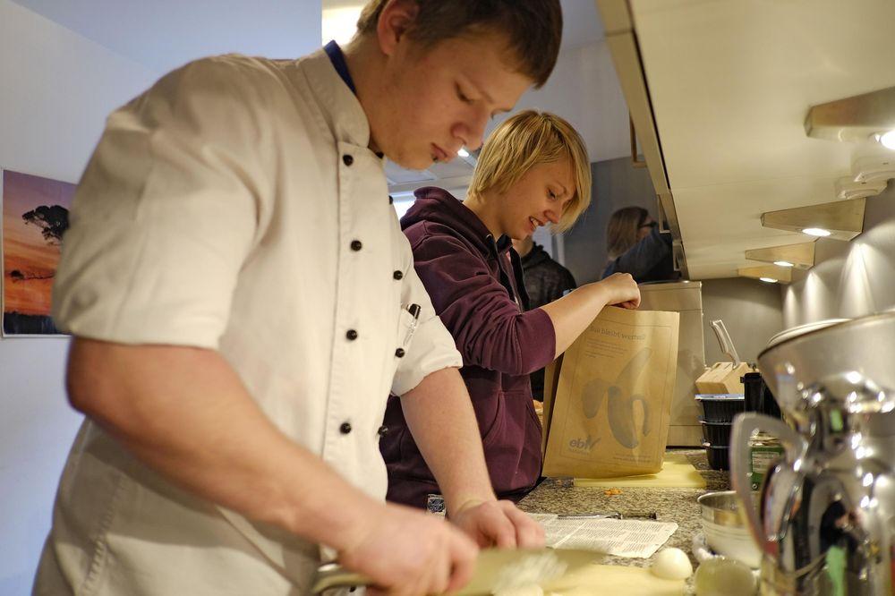 Ein junger Mann schneidet in Küchenkleidung Zwiebeln. Eine Frau steht neben ihm und packt weitere Lebensmittel aus einer Papiertüte aus.