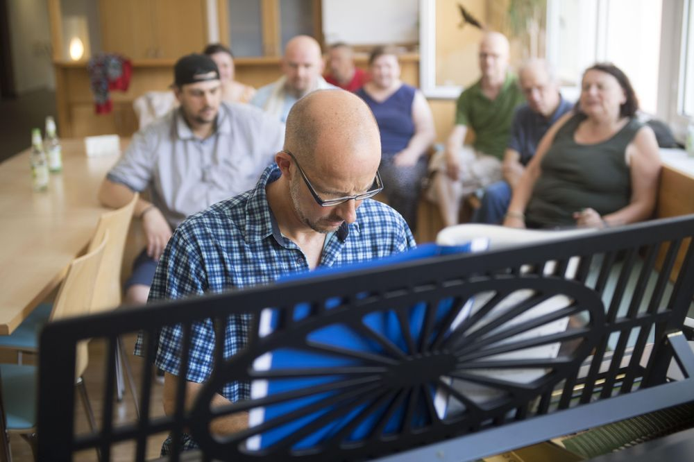 Die Bewohner*innen des Maria-Augsten-Hauses hören einem Mann zu, der am Klavier spielt.
