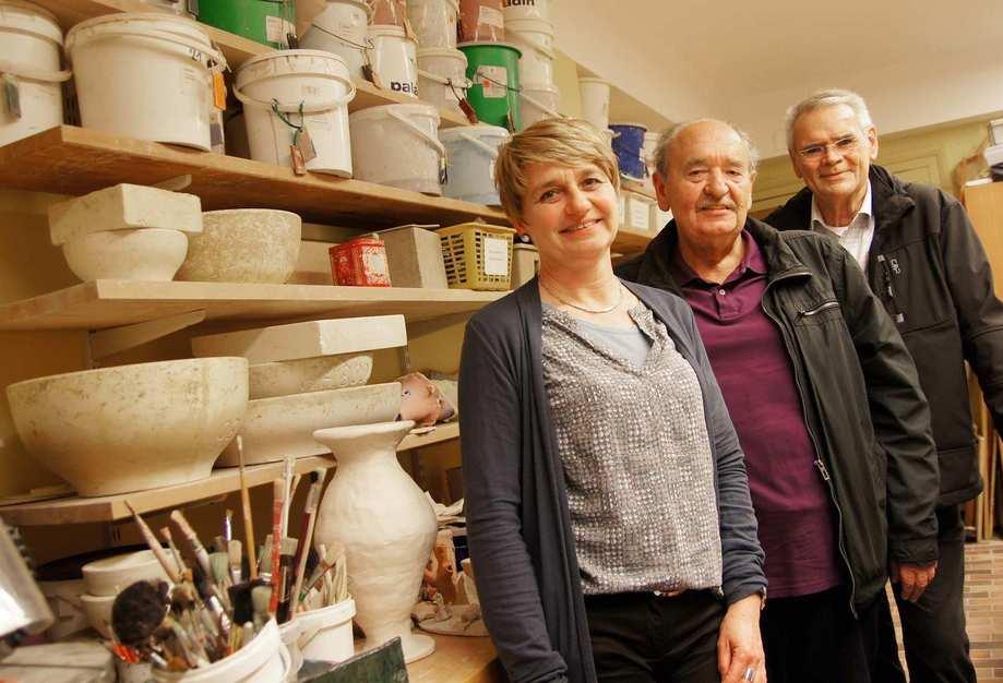 In einer Werkstatt: Ein Frau und zwei ältere Männer lächeln.
