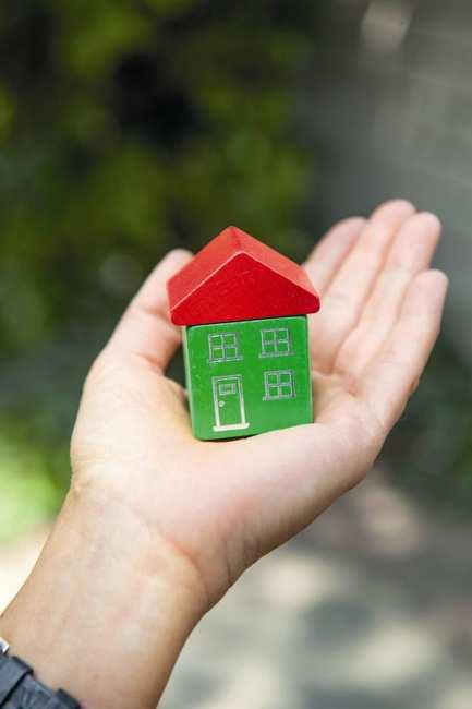 Eine geöffnete Hand hält ein kleines Haus aus Holzbauklötzchen.