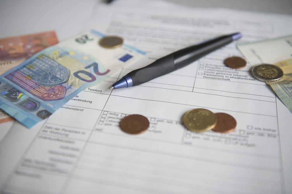 Ein ausgedruckter Antrag, auf dem ein Kugelschreiber, Geldmünzen und ein 20 Euro Schein liegen