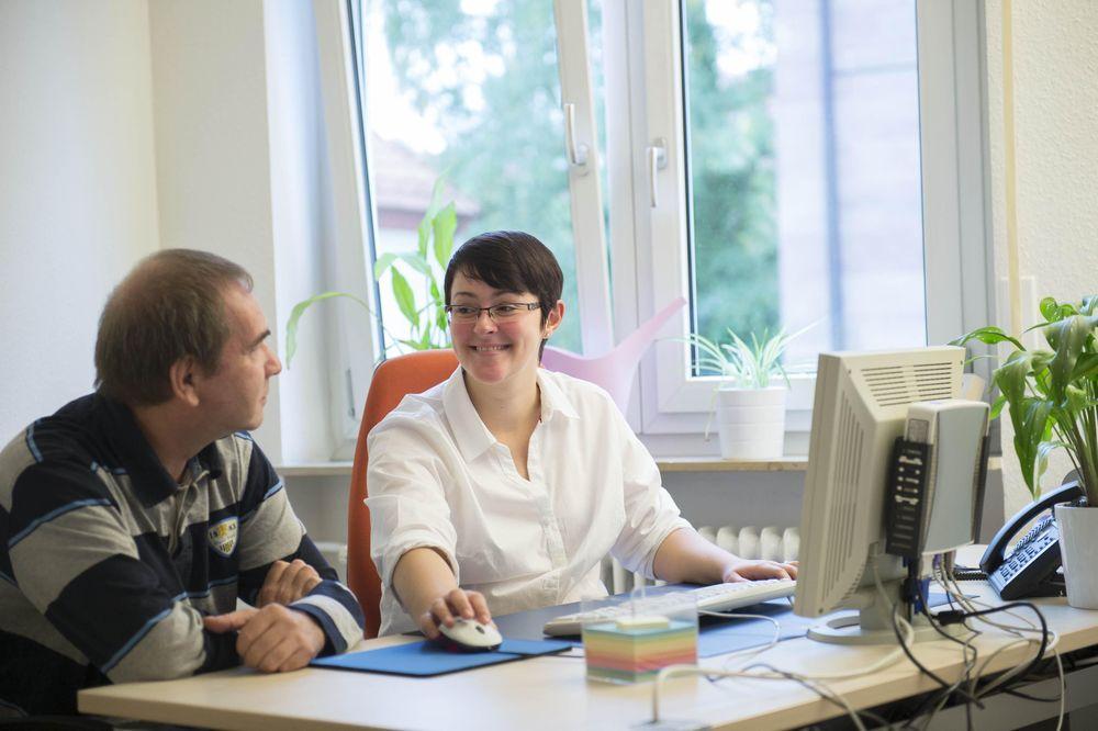 Eine Frau und ein Mann sitzen vor einem Computer und lächeln sich an.