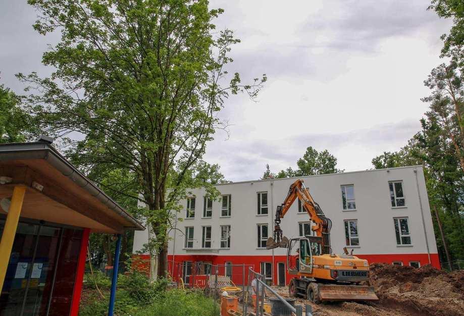 Vor einem rot-weiß gestrichenem Gebäude steht ein Bagger.