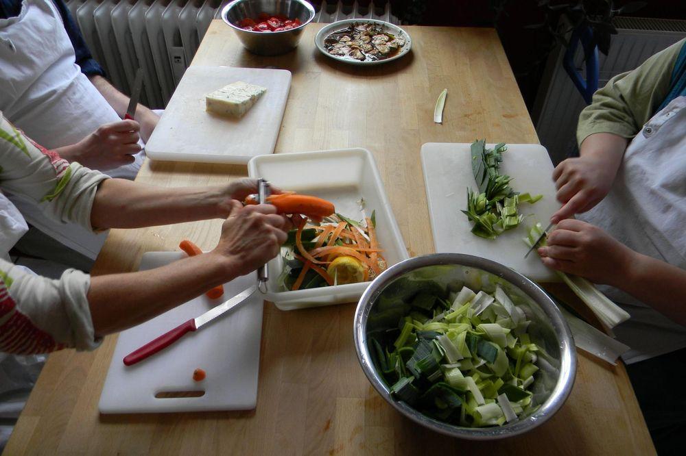 Personen die Gemüse schneiden und schälen