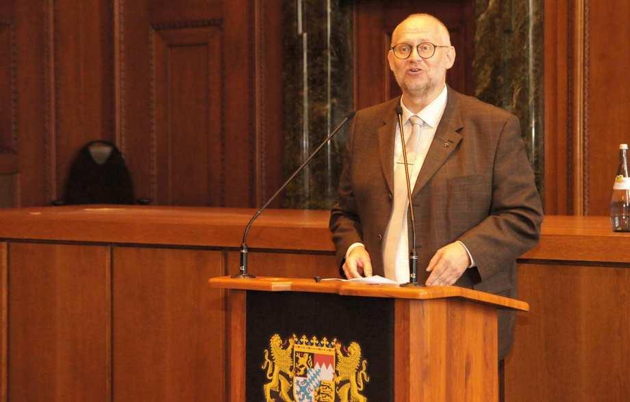Ein älterer Mann im Anzug steht an einem Rednerpult.