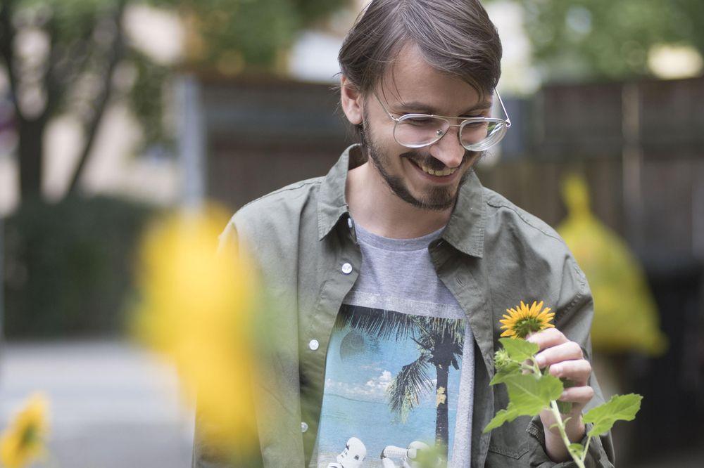Ein lächelnder Mann hält eine Sonnenblume in der Hand.