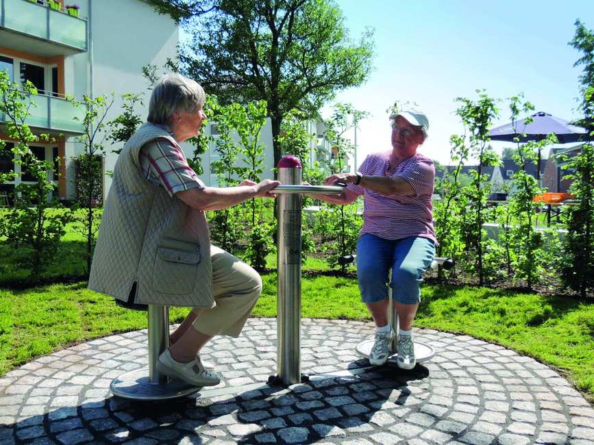 Zwei ältere Damen sitzen sich auf drehbaren Metallhockern gegenüber.