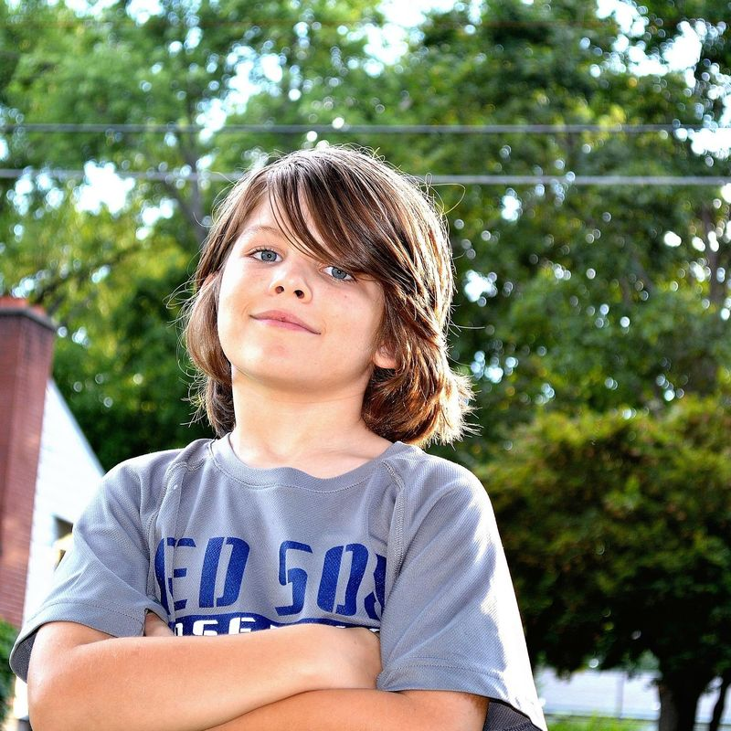 Ein braunhaariger Junge, mit verschränkten Armen grinst in die Kamera
