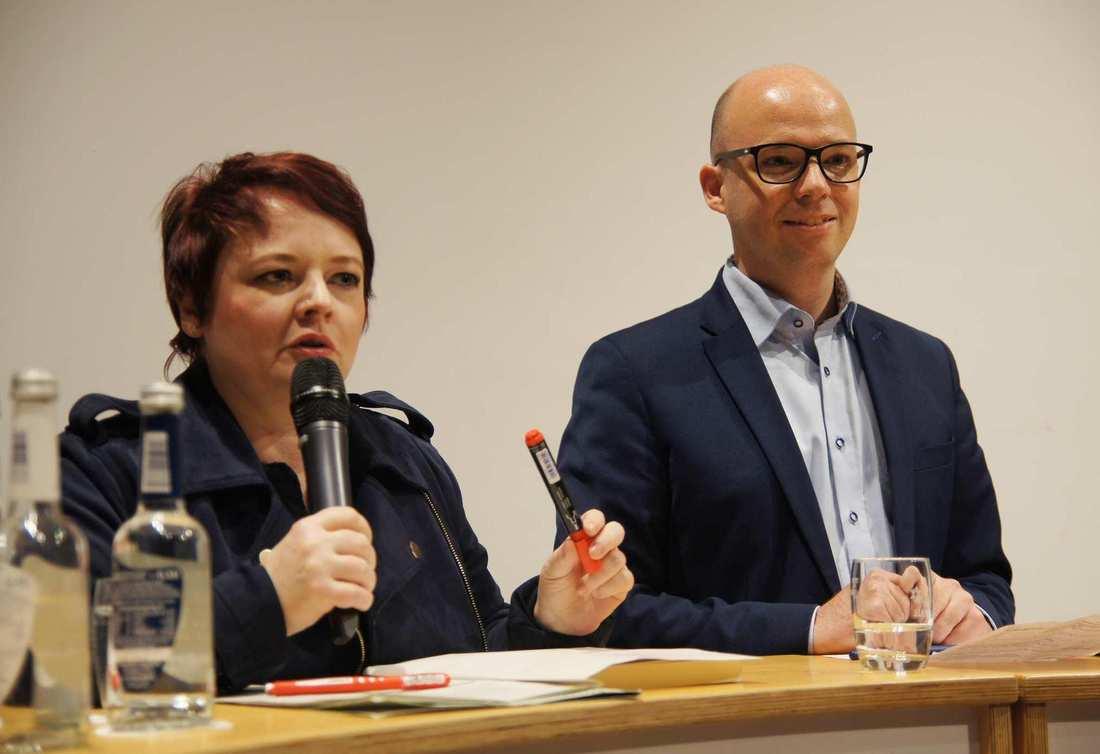 Verena Osgyan und Thorsten Brehm am Pult. Osgyan spricht ins Mikro. Brehm lächelt.