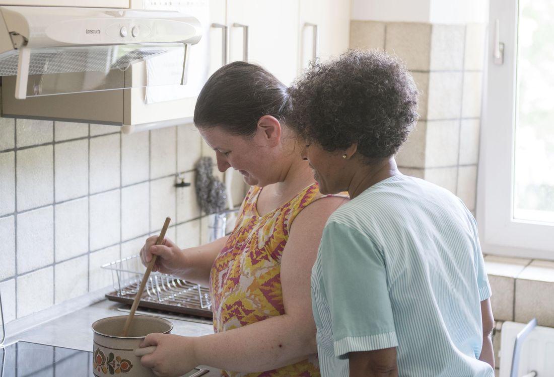Eine Hauswirtschaftskraft und eine Bewohnerin kochen zusammen.