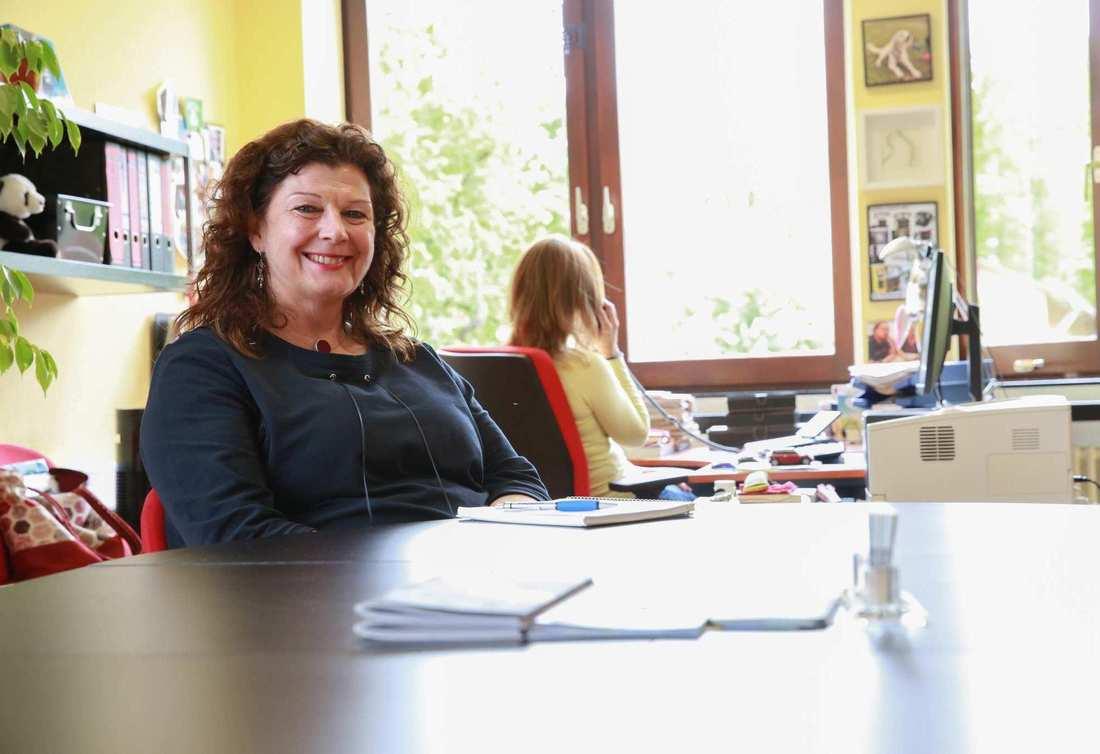 An einem Tisch sitzt Birgit Dier, eine lächelnde Frau mit braunen Locken. Im Hintergrund sitzt eine Frau am Telefon. Sie dreht uns den Rücken zu.