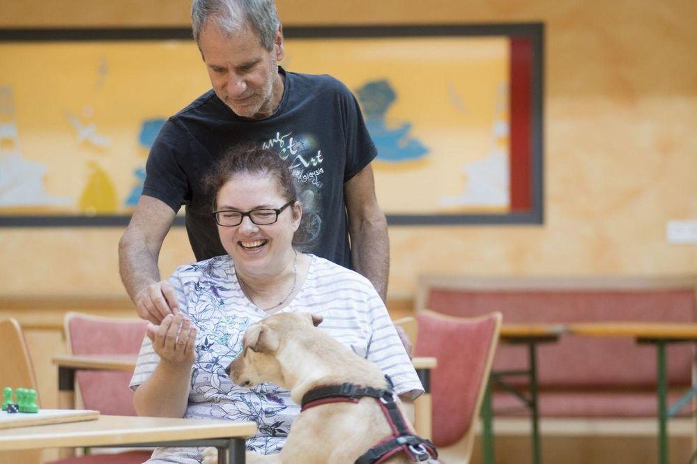 Eine jüngere Heimbewohnerin und ein Mitarbeiter spielen mit einem Hund.
