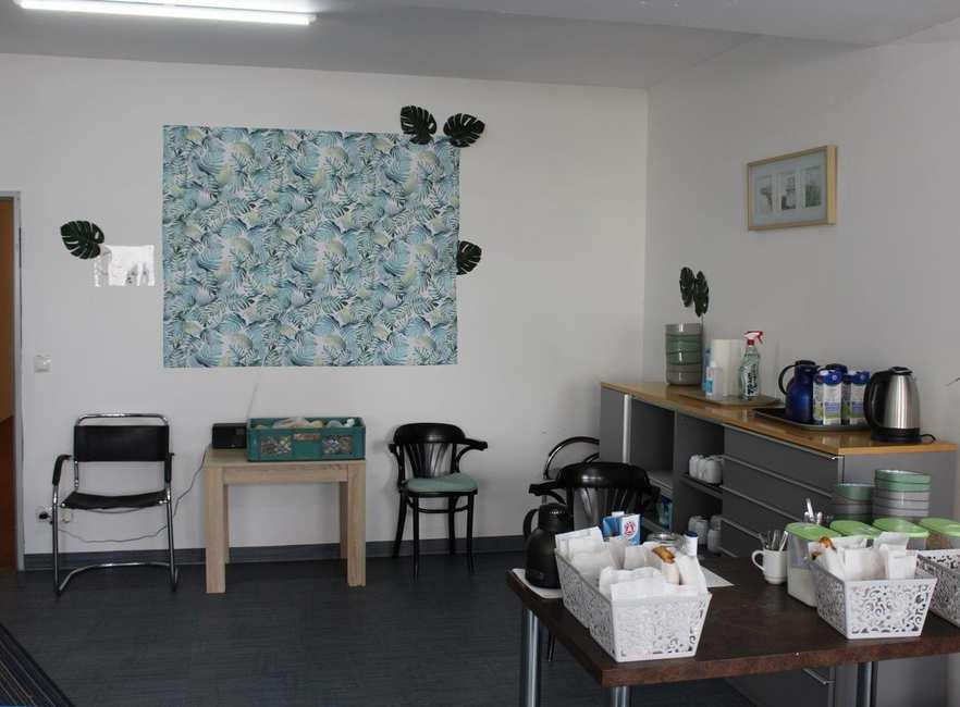 Ein Raum mit Stühlen und Tischen. Tee, Kaffee, Müsli und Frühstückstüten stehen bereit.