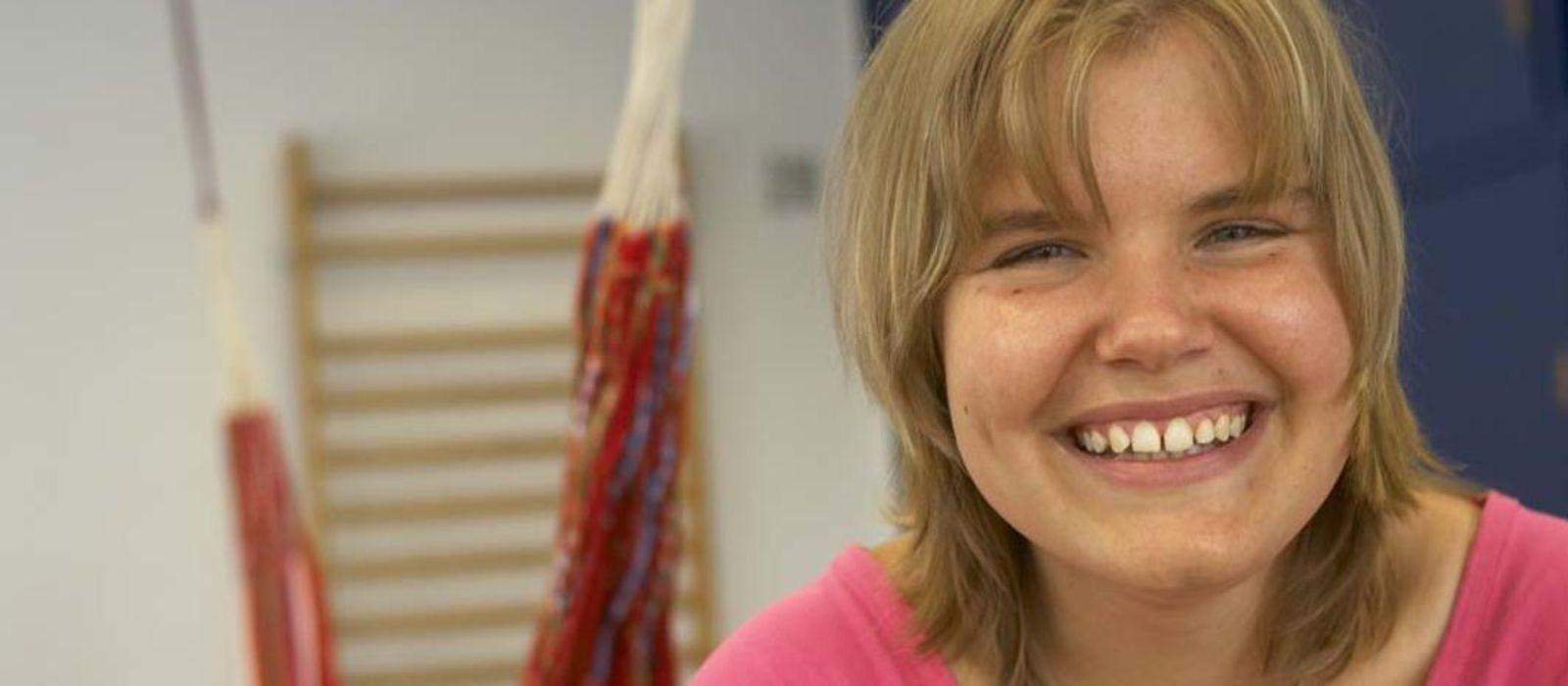 Ein Mädchen in einem pinken Tshirt lacht in die Kamera.