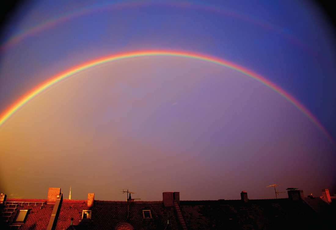 Ein Regenbogen steht über einer Dachsilhouette am dunkelblauen Himmel.