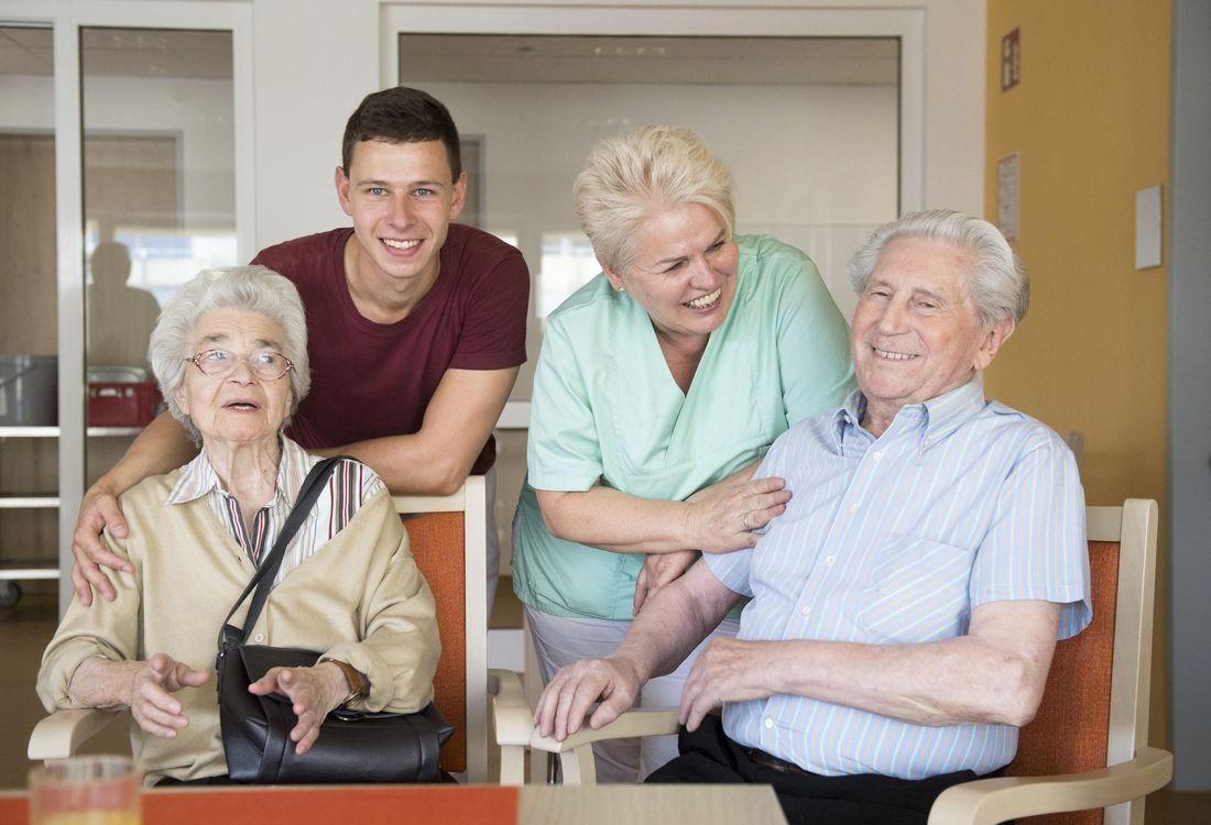 Zwei Pflegefachkräfte und zwei Senioren*innen sitzen beieinander und lächeln.